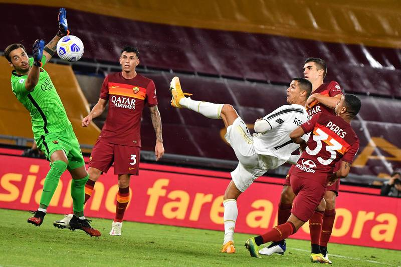 Juventus' Portuguese forward Cristiano Ronaldo (3rdR) eyes the ball as he scores an equalizer past Roma's Italian goalkeeper Antonio Mirante (L) during the Italian Serie A football match Roma vs Juventus on September 27, 2020 at the Olympic stadium in Rome. (Photo by Tiziana FABI / AFP)