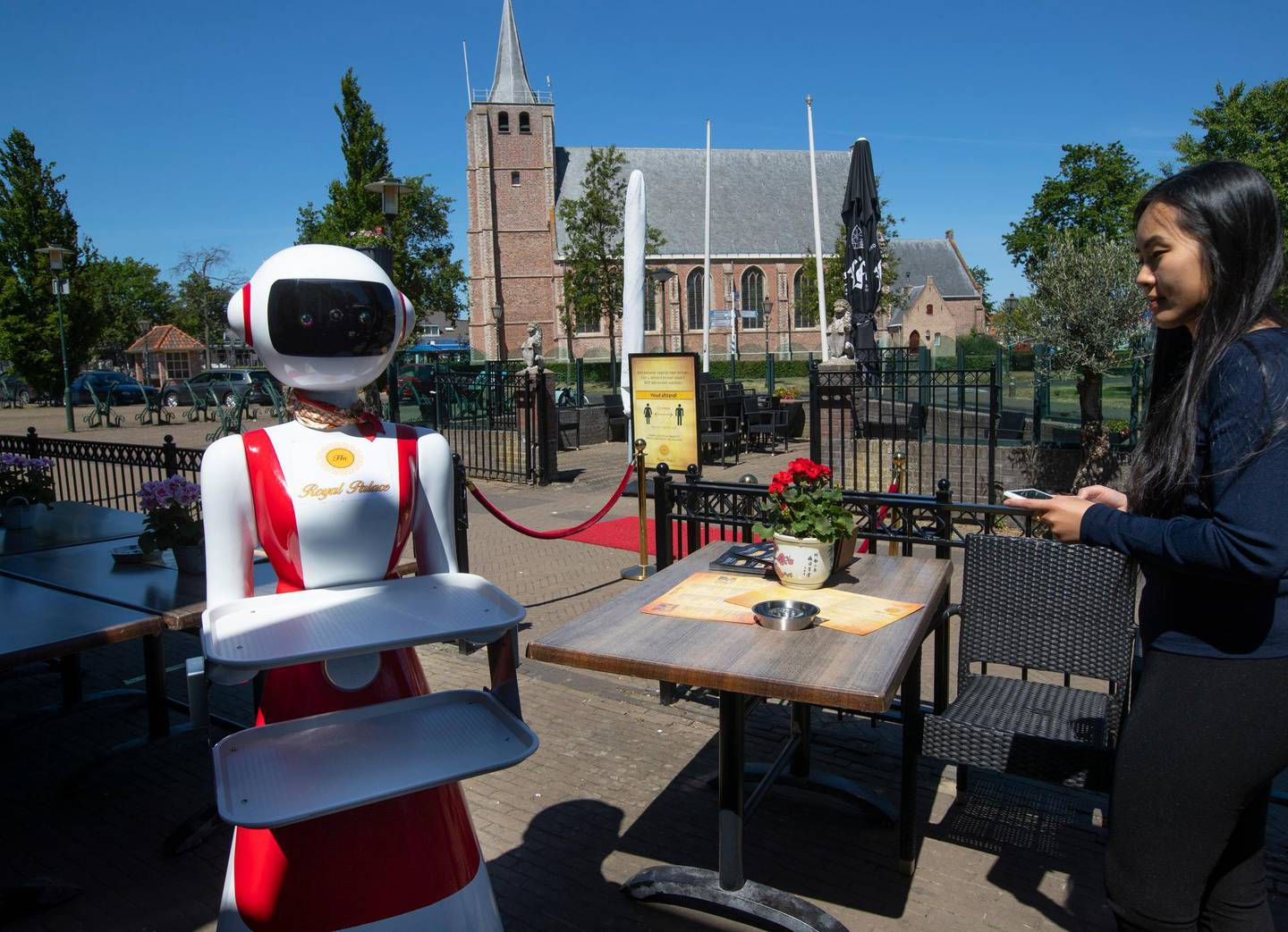 Leah Hu uses a tablet to demonstrate the use of a robot for serving purposes or for dirty dishes collection, as part of a tryout of measures to respect social distancing and help curb the spread of the COVID-19 coronavirus, at the family's Royal Palace restaurant in Renesse, south-western Netherlands, Wednesday, May 27, 2020. (AP Photo/Peter Dejong)