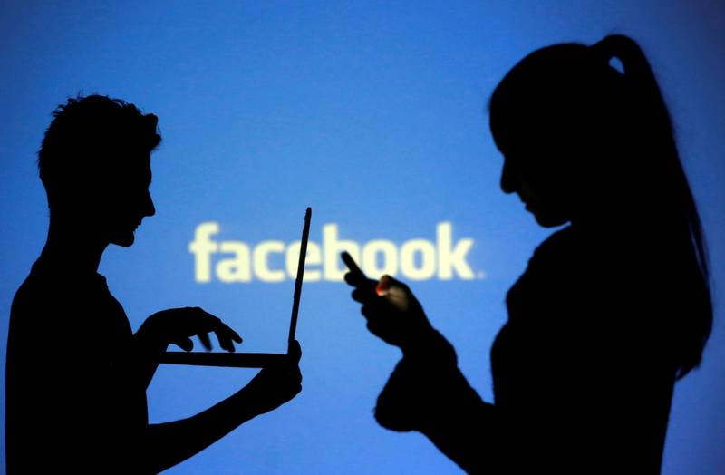FILE PHOTO: People are silhouetted as they pose with laptops in front of a screen projected with a Facebook logo, in this picture illustration taken in Zenica, October 29, 2014. REUTERS/Dado Ruvic/File Photo