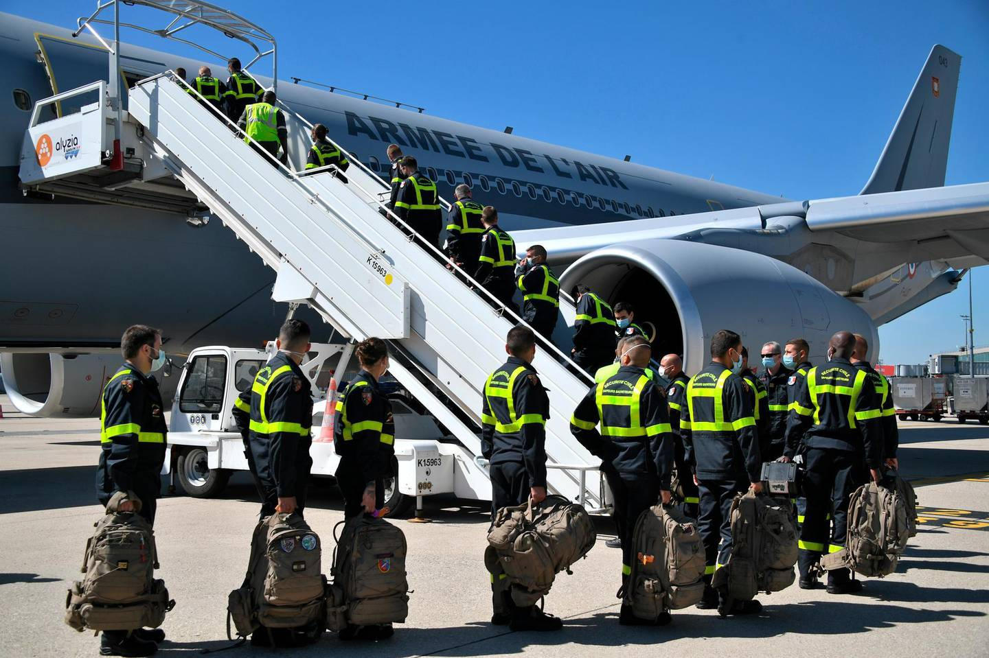 French Securite Civile rescue workers board a military plane at Roissy airport, north of Paris, Wednesday, Aug. 5, 2020. The French emergency workers traveling to Lebanon include members of a special unit with chemical and other technological expertise trained to intervene in damaged industrial sites. French President Emmanuel Macron announced he would fly to the shattered Lebanese capital, and two planeloads of French rescue workers and aid were expected to touch down on Wednesday afternoon. (Bertrand Guay, Pool via AP)