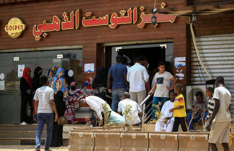 Residents of the Sudanese capital Khartoum queue in front of a bakery, on April 9, 2020. - The Sudanese authorities yesterday announced a rise in the price of bread in the capital, nearly a year after the fall of president Omar al-Bashir. A tripling of the price of bread had been the trigger for street protests against Bashir in December 2018 (Photo by ASHRAF SHAZLY / AFP)