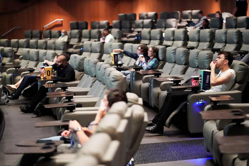 """FILE PHOTO: People take their seats inside the Odeon Luxe Leicester Square cinema, on the opening day of the film """"Tenet"""", amid the coronavirus disease (COVID-19) outbreak, in London, Britain, August 26, 2020. REUTERS/Henry Nicholls/File Photo"""