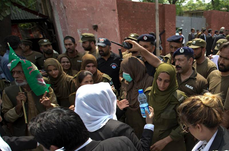 Police officers hold back supporters of Pakistan's jailed ex-Prime Minister Nawaz Sharif as they gather outside the Adiala jail where he is being held, in Rawalpindi, Pakistan, Thursday, July 19, 2018. A spokesman for the political party of Sharif, the Pakistan Muslim League, said Thursday that the former leader is being held in deplorable conditions as he awaits the outcome of his appeal over a 10-year sentence on corruption charges. (AP Photo/B.K. Bangash)