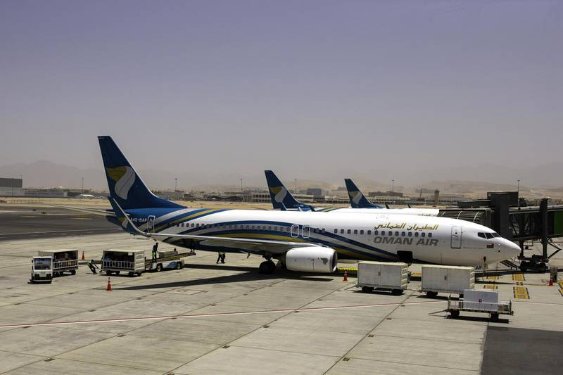 A Boeing Co. 737-800 aircraft, operated by Oman Air, stands beside the passenger terminal at Muscat International Airport in Muscat, Oman, on Monday, May 7, 2018. Being the Switzerland of the Gulf served the country well over the decades, helping the sultanate survive, thrive and make it a key conduit for trade and diplomacy in the turbulent Middle East.��Photographer: Christopher Pike/Bloomberg