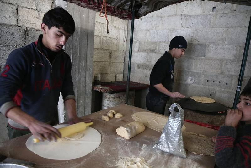 """Syrian youth prepare bread as they take shelter inside a building in Haza, in the  besieged Eastern Ghouta region on the outskirts of the capital Damascus on February 27, 2018. - A humanitarian """"pause"""" announced by Russia in Syria's deadly bombardment of Eastern Ghouta struggled to take hold, with fresh violence erupting and no sign of aid deliveries or residents leaving the besieged enclave. (Photo by ABDULMONAM EASSA / AFP)"""