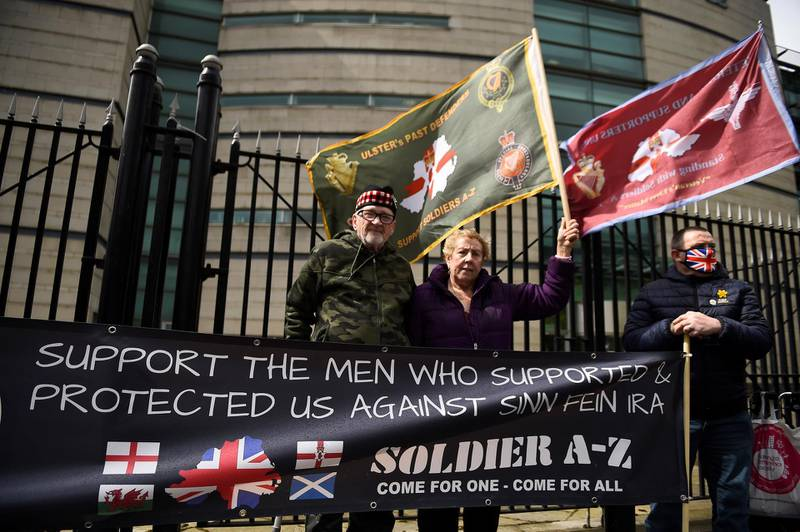 People hold flags and a banner outside Laganside Courts during the trial into the 1972 killing of official IRA member Joe McCann, in Belfast, Northern Ireland, May 4, 2021. REUTERS/Clodagh Kilcoyne