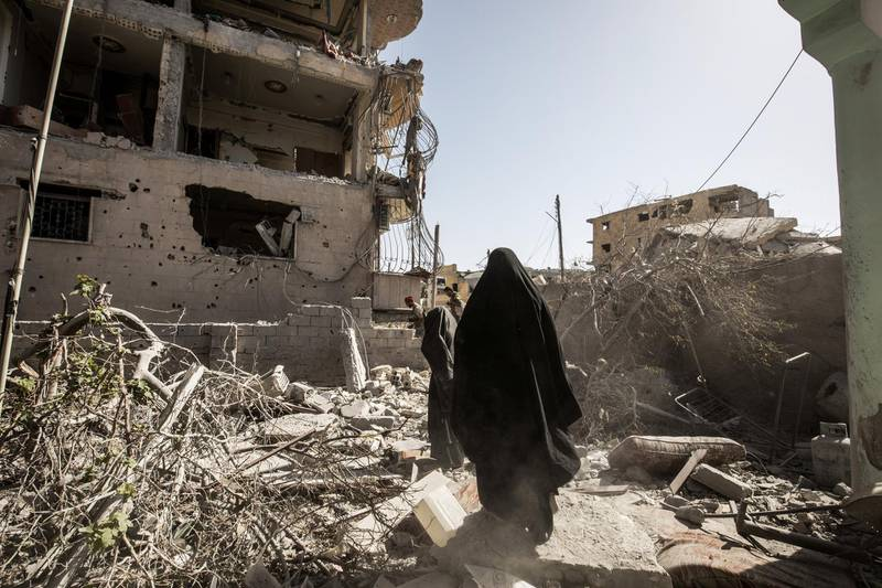 RAQQA, SYRIA - 2017/10/08: Civilians walks up through city ruins while fleeing fighting in Islamic state controlled area. More than a thousand dead and a city in ruins. The Syrian civil war has been carried on for more than 6 years and it has caused more than 450,000 deaths and over 5 million people has made to become refugees. There is still no ending to this conflict in sight. (Photo by Afshin Ismaeli/SOPA Images/LightRocket via Getty Images)