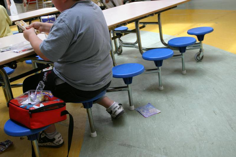 ABWB6E An overweight boy eats snacks for lunch at school, London, UK.. Image shot 2004. Exact date unknown.