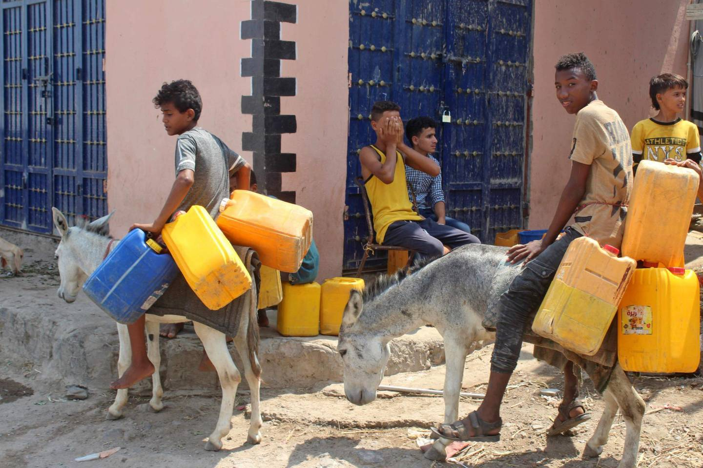 Yemeni youths commute on donkeys carrying plastic jerrycans in the southern city of Aden, on September 16, 2020. Yemenis are resorting to using donkeys to transport water and haul goods, as the long years of conflict that have ravaged the economy make gas-guzzling vehicles unaffordable for many. / AFP / Saleh Al-OBEIDI