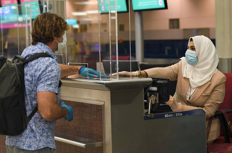 A passenger of an Emirates airlines flight departing to the Australian city of Sydney, checks in at Dubai International Airport on May 22, 2020, after the resumption of scheduled operations by the Emirati carrier, amid the ongoing novel coronavirus pandemic crisis.       / AFP / Karim SAHIB