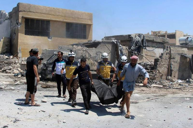 This Thursday, June. 20, 2019 file photo provided by the Syrian Civil Defense White Helmets, which has been authenticated based on its contents and other AP reporting, shows Civil Defense workers and civilians carrying a body after airstrikes by Syrian government forces hit the town of Hish in Idlib province, Syria. Two members of the opposition's Syrian Civil Defense were killed and four were wounded Wednesday, June 26, 2019 when an airstrike struck their ambulance in northwestern Syria as violence claimed more lives in the last major rebel stronghold in the country, the Civil Defense and opposition activists said. (Syrian Civil Defense White Helmets via AP, File)