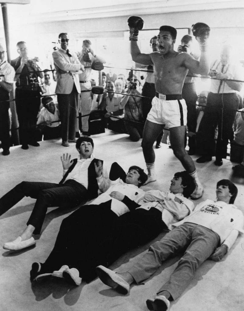February 1964:  American heavyweight boxer Cassius Clay poses in the ring in mock victory over British pop group The Beatles, meeting the press in New York during an American tour.  (Photo by Keystone/Getty Images)