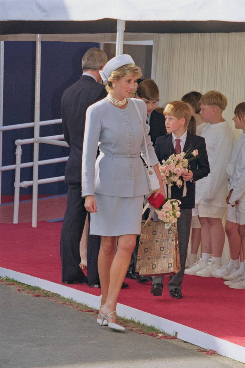 British Royal Diana, Princess of Wales (1961-1997), wearing a light blue suit and matching pillbox hat, with a multi-strand pearl necklace, and her son Prince Harry attending the Heads of State Victory in Europe Remembrance Service, marking the 50th anniversary of VE Day, in Hyde Park, London, England, 7th May 1995. (Photo by Princess Diana Archive/Hulton Archive/Getty Images)