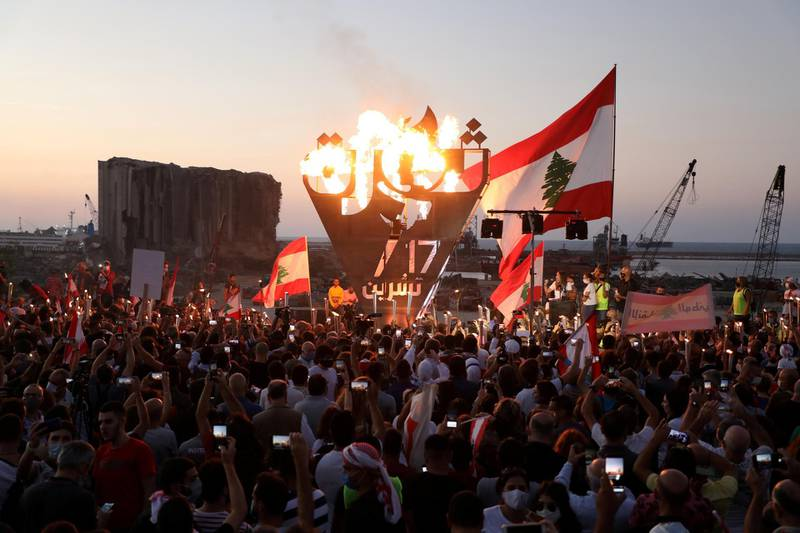"""FILE PHOTO: Anti-government demonstrators take pictures of a metal sculpture spelling out the word """"revolution"""" topped by flames during a protest as Lebanese mark one year since the start of nation-wide protests, near Beirut's port, Lebanon October 17, 2020. REUTERS/Mohamed Azakir/File Photo"""