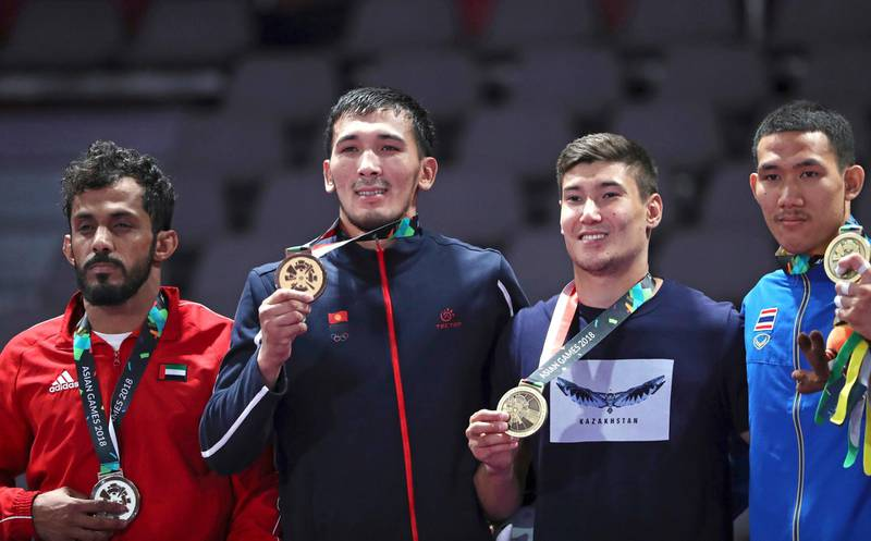 Medalists from left to right, Talib Alkirbi of United Arab Emirates, with silver, Torokan Bagynbai Uulu of Kyrgyzstan, with gold, Nartay Kazhekov of Kazakhstan and Banpot Lertthaisong of Thailand, with bronze during the victory ceremony of men's -69 kilogram jujitsu at the 18th Asian Games in Jakarta, Indonesia, Friday, Aug. 24, 2018. (AP Photo/Firdia Lisnawati)