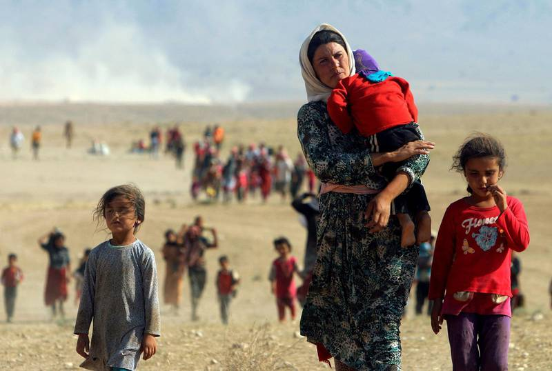 """Displaced people from the minority Yazidi sect, fleeing violence from forces loyal to the Islamic State in Sinjar town, walk towards the Syrian border, on the outskirts of Sinjar mountain, near the Syrian border town of Elierbeh of Al-Hasakah Governorate, Iraq, August 11, 2014. Picture taken August 11, 2014. REUTERS/Rodi Said/File Photo SEARCH """"POY DECADE"""" FOR THIS STORY. SEARCH """"REUTERS POY"""" FOR ALL BEST OF 2019 PACKAGES. TPX IMAGES OF THE DAY."""
