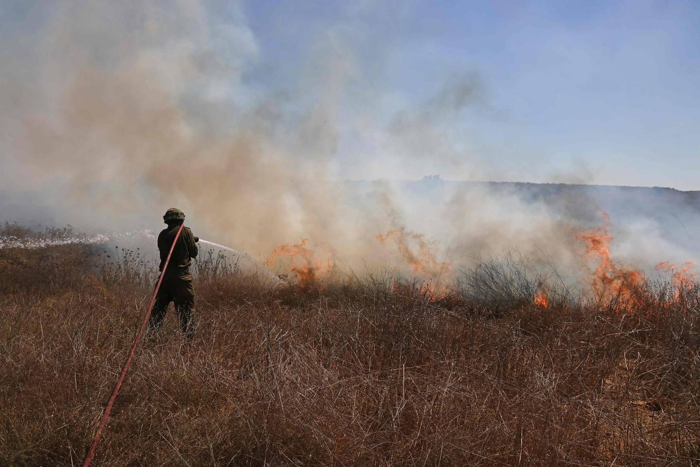 An Israeli soldier extinguishes a fire in a field close to the southern kibbutz of Nir Am near the border with the Gaza Strip on August 25, 2020, after it was set off by incendiary balloons launched from the Palestinian enclave. / AFP / menahem kahana