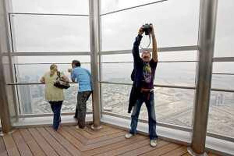 Dubai - January 5, 2010 - Mladjan Sladakovic makes a self portrait while others view Dubai from the 124th floor observation deck of the Burj Khalifa in Dubai, January 5, 2010. (Photo by Jeff Topping/The National)   *** Local Caption ***  JT001-0105-BURJ KHALIFA_MG_9857.jpg
