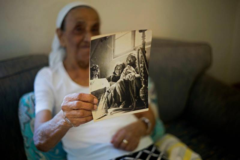 FILE - In this July 11, 2016 file photo, Yemen born Jewish Israeli Yona Josef holds a photograph dated back to the 1940's of her and her father back in Yemen in her home in Raanana, Israel. Josef said she was asked to take her 4-year-old sister Saada to a health clinic and leave her there. When she returned several hours later, she was told her sister was dead and the family was given no further details or a body to bury. The Israeli government has approved a plan to offer $50 million in compensation to the families of hundreds of Yemenite children who disappeared in the early years of the country's establishment. But the announcement on Monday, Feb. 22, 2021, received a cool reception from advocacy groups that said the government had failed to apologize or accept responsibility for the affair. (AP Photo/Ariel Schalit, File)