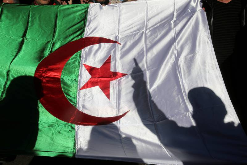 FILE PHOTO: A demonstrator's shadow is cast on a national flag during an anti-government rally in Algiers, Algeria December 24, 2019. REUTERS/Ramzi Boudina/File Photo