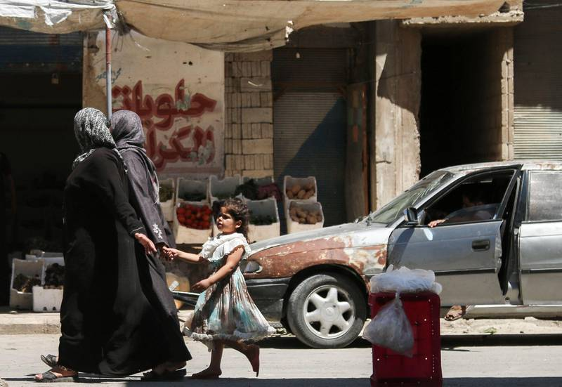 A Syrian girl holds a woman's hand as she walks down a street in the central Syrian rebel-held town of Talbiseh, north of Homs on August 3, 2017.  A ceasefire between government forces and rebels went into effect in part of central Syria on August 3, 2017 after Russia struck a deal with the opposition on a safe zone in the northern parts of Homs province.  The truce is the third to be established in Syria, which has been ravaged by six years of civil war that have left more than 300,000 people dead. / AFP PHOTO / MAHMOUD TAHA