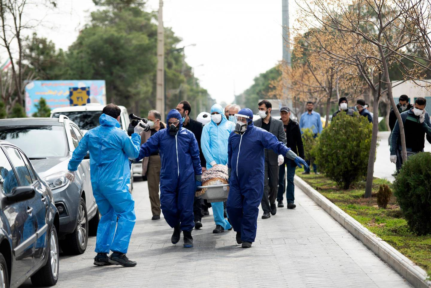 FILE— In this Sunday, March 8, 2020 file photo, men wearing protective gear carry the body of Fatemeh Rahbar, a lawmaker-elect from Tehran constituency, who died on Saturday after being infected with the new coronavirus, at Behesht-e-Zahra cemetery, just outside Tehran, Iran. Nine out of 10 cases of the virus in the Middle East come from the Islamic Republic. For most people, the new coronavirus causes only mild or moderate symptoms. For some it can cause more severe illness. (Mehdi Khanlari/Fars News Agency via AP, File)