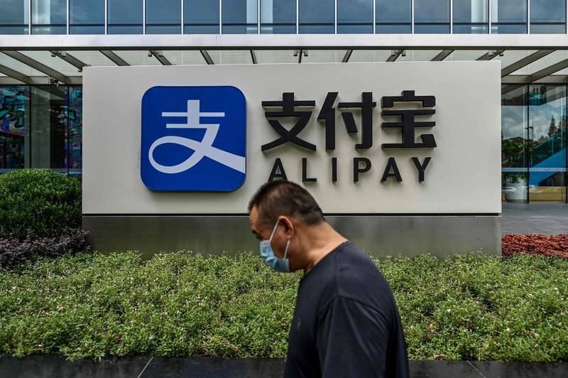 (FILES) This file photo taken on August 28, 2020 shows a pedestrian walking past an Alipay logo at the Shanghai office building of Ant Group in Shanghai.  US President Donald Trump on January 5, 2021 ordered a ban on Alipay, WeChat Pay and other apps linked to Chinese companies, saying they could route user information to the government in Beijing. / AFP / HECTOR RETAMAL