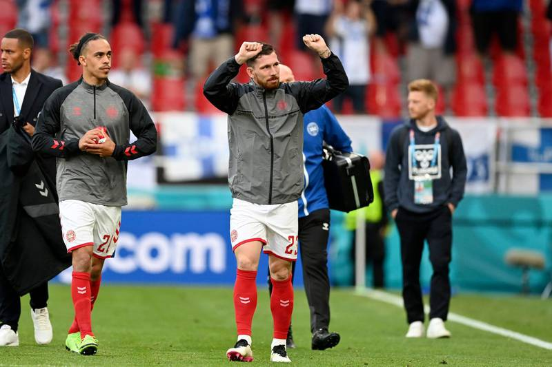 Denmark's Pierre-Emile Hojbjerg gestures to the stands as the team returns to the pitch to resume the match suspended earlier when Denmark's Christian Eriksen collapsed on the pitch and had to be taken to hospital during the Euro 2020 soccer championship group B match between Denmark and Finland at Parken Stadium in Copenhagen, Saturday, June 12, 2021. (Stuart Franklin/Pool via AP)