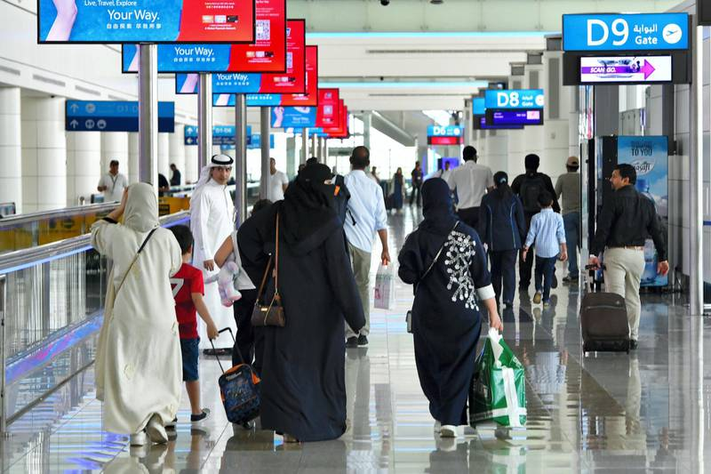 A picture take on September 14, 2017 shows people walking at Dubai's International Airport . / AFP PHOTO / GIUSEPPE CACACE