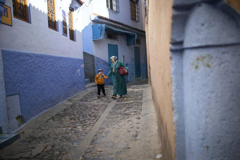 A mother walks with her son down an alleyway deserted of tourists in Chefchaouen, northern Morocco, Saturday, Dec. 26, 2020. The picturesque town, its facades painted in distinctive hues of blue, shut its small population off from the world, and kept the virus out for months. Now, as the country cautiously reopens and tries to resuscitate its struggling economy, Chefchaouen stands subdued, deserted by the tourists that have long been its lifeblood. (AP Photo/Mosa'ab Elshamy)