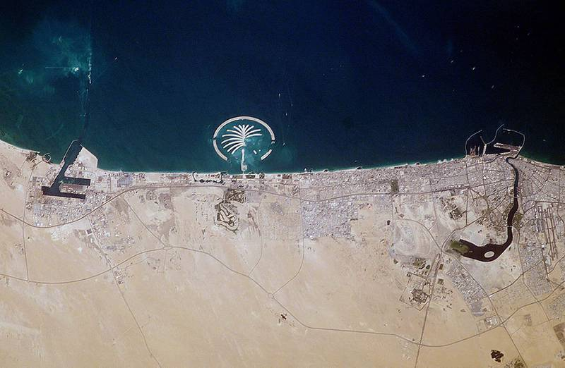 This NASA file image obtained 13 July, 2003, captured by the crew of the International Space Station in March, 2003, shows Palm Island (C) along the coast of Dubai in the United Arab Emirates. Palm Island Resort, just 1 mile off the coast from Dubai, is scheduled to be complete by 2006. Advertised as being visible from the Moon this man-made structure will have 17 huge fronds surrounded by a crescent-shaped breakwater. This island is being built from 80 million cubic meters (2.8 billion cubic feet) of land dredged from the approach channel to the Emirate's Jebel Ali port, which is being deepened to 17 meters (56 feet). Sediments in the water from dredging activity can be seen near the port. Palm Island is one of several massive projects in Dubai aimed at diversifying the economic base by expanding the tourist industry. The government of Dubai predicts that tourism, mostly from Europe, will quadruple to 15 million visitors annually by 2010. When completed the resort will have approximately 1200 single-family residences each with private beach front, 600 multi-family residences, an aquatic theme park, shopping centers, cinemas, and more. A twin island is planned to be built nearby.     AFP PHOTO/NASA (Photo by NASA / NASA / AFP)