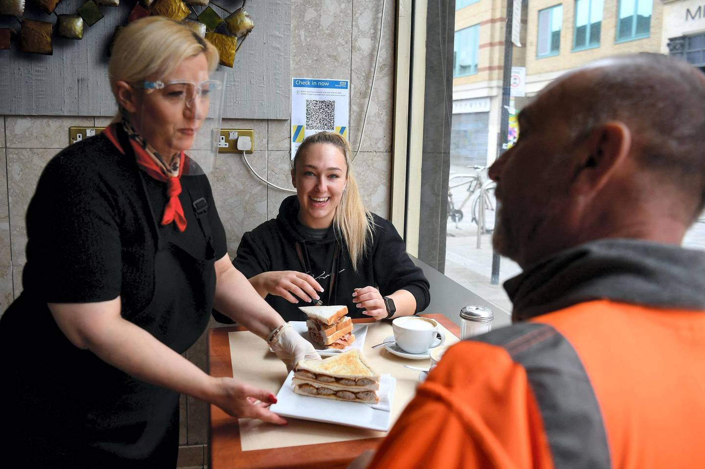 A worker places a customer's breakfast order of a sausage sandwich at a table inside Barbarella's cafe in London as Covid-19 lockdown restrictions ease across the country on May 17, 2021. / AFP / DANIEL LEAL-OLIVAS