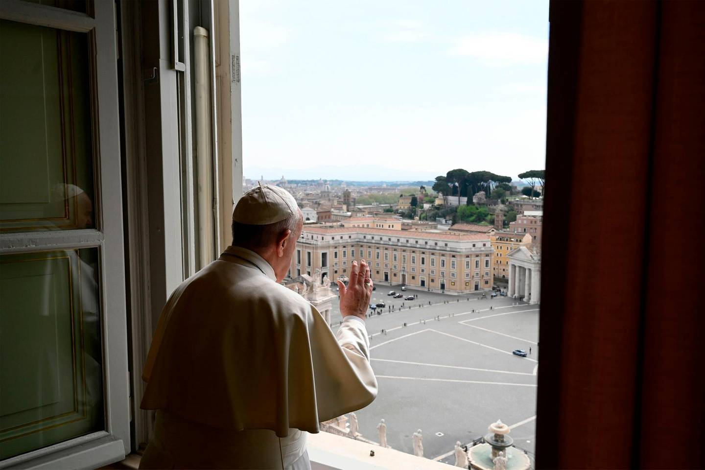 """This photo taken and released on April 13, 2020 by the Vatican Media shows Pope Francis deliver his blessing from the window of the Apostolic palace after deliver his message during a private Angelus prayer live broadcast from the palace's library in the Vatican on Easter Monday, during the lockdown aimed at curbing the spread of the COVID-19 infection, caused by the novel coronavirus.  RESTRICTED TO EDITORIAL USE - MANDATORY CREDIT """"AFP PHOTO / VATICAN MEDIA"""" - NO MARKETING - NO ADVERTISING CAMPAIGNS - DISTRIBUTED AS A SERVICE TO CLIENTS  / AFP / VATICAN MEDIA / Handout / RESTRICTED TO EDITORIAL USE - MANDATORY CREDIT """"AFP PHOTO / VATICAN MEDIA"""" - NO MARKETING - NO ADVERTISING CAMPAIGNS - DISTRIBUTED AS A SERVICE TO CLIENTS"""