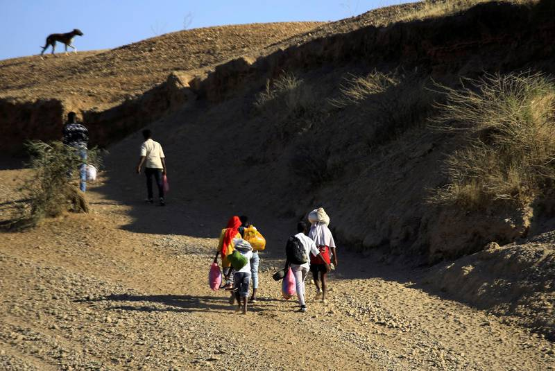 FILE PHOTO: Ethiopians, who fled the ongoing fighting in Tigray region, carry their belongings after crossing the Setit River on the Sudan-Ethiopia border, in the eastern Kassala state, Sudan December 16, 2020. REUTERS/Mohamed Nureldin Abdallah/File Photo