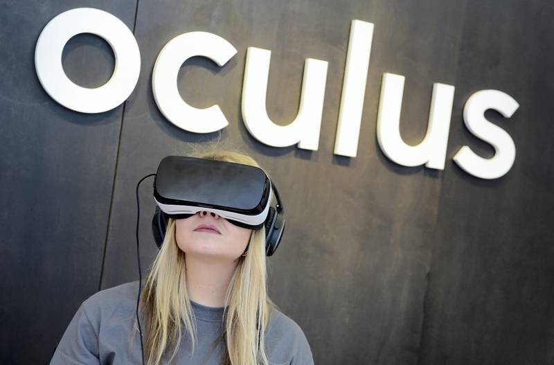 """A woman use an """"Oculus VR"""" virtual reality device during a press preview of the """"Facebook Innovation Hub"""" in Berlin on February 24, 2016. / AFP PHOTO / TOBIAS SCHWARZ"""