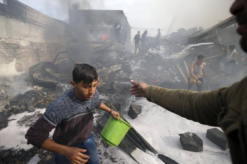 A young Palestinian uses buckets filled with water to help put out a fire that broke out in a market in the refugee camp of Nuseirat in central Gaza Strip, on March 5, 2020. / AFP / MOHAMMED ABED