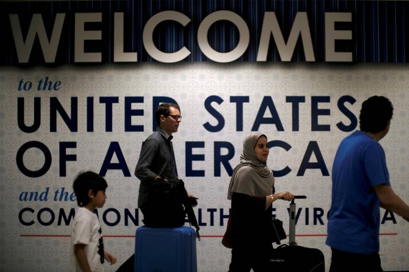 FILE PHOTO: International passengers arrive at Washington Dulles International Airport after the U.S. Supreme Court granted parts of the Trump administration's emergency request to put its travel ban into effect later in the week pending further judicial review, in Dulles, Virginia, U.S., June 26, 2017. REUTERS/James Lawler Duggan/File Photo