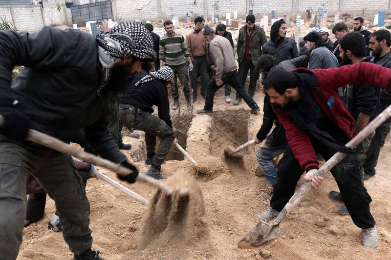 Syrians bury bodies during a group funeral ceremony at a cemetery following reported airstrikes on January 7, 2016 in the rebel-held city of Douma, northeast of the capital Damascus. More than 260,000 people have been killed since the Syrian conflict erupted in March 2011 and millions forced from their homes. (Photo by AMER ALMOHIBANY / AFP)