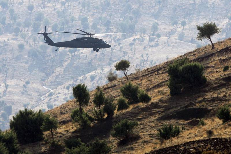 """(FILES) In this file photo taken on October 31, 2007 a Turkish army helicopter flies over  mountains in the province of Sirnak, near the Turkish-Iraqi border, south-eastern Turkey. Turkey launched an air and ground offensive against Kurdish rebels in northern Iraq on June 17, 2020 in a move likely to increase friction with the Baghdad government. The defence ministry said """"commandos""""  moved in supported by drones and helicopters, following a bombardment with rocket launchers and artillery guns that hit more than 150 targets. / AFP / MUSTAFA OZER"""