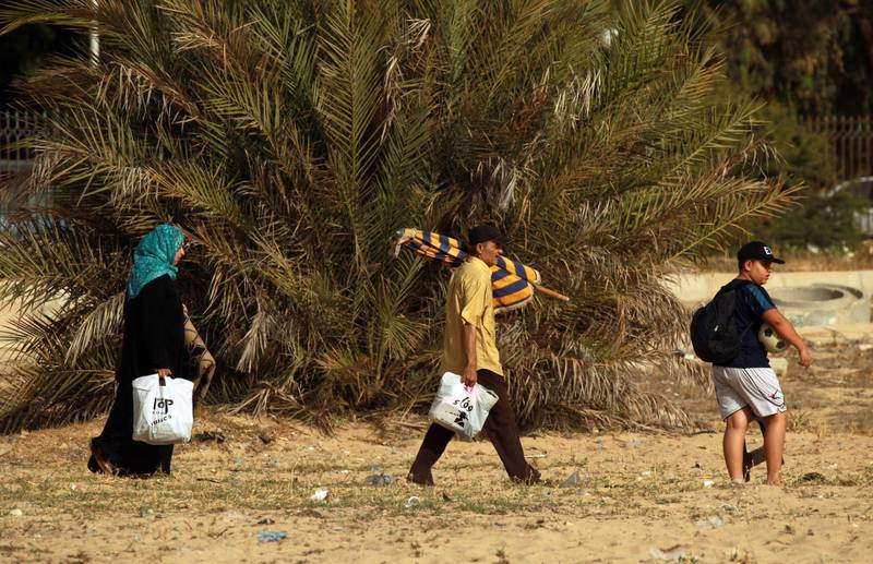 People carrying bags and an umbrella arrive at the beach, along the coast of the eastern Libyan port city of Benghazi on June 20, 2020.  / AFP / Abdullah DOMA