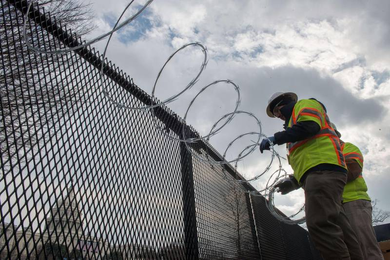 WASHINGTON, DC - JANUARY 15: Crews install razor wire on top of the fencing that now surrounds the US Capitol ahead of the inauguration on January 15, 2021 in Washington, DC. After last week's Capitol Riot the FBI has warned of additional threats against the US Capitol and in all 50 states.   Liz Lynch/Getty Images/AFP == FOR NEWSPAPERS, INTERNET, TELCOS & TELEVISION USE ONLY ==
