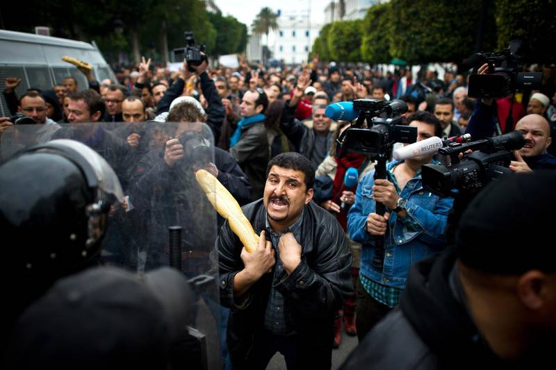 """A Tunisian protester holding a baguette talks to riot policemen during a demonstration in Tunis on January 18, 2011. Riot police fired tear gas and clashed with protesters on January 18 at a small protest rally against Tunisia's new government in the centre of the capital, AFP reporters on the ground saw. Around 100 protesters chanted slogans against the RCD party of ousted president Zine El Abidine Ben Ali. """"We can live on bread and water alone but not with the RCD,"""" they said. Riot police dispersed the rally -- one of several expected on Tuesday.  AFP PHOTO / MARTIN BUREAU"""