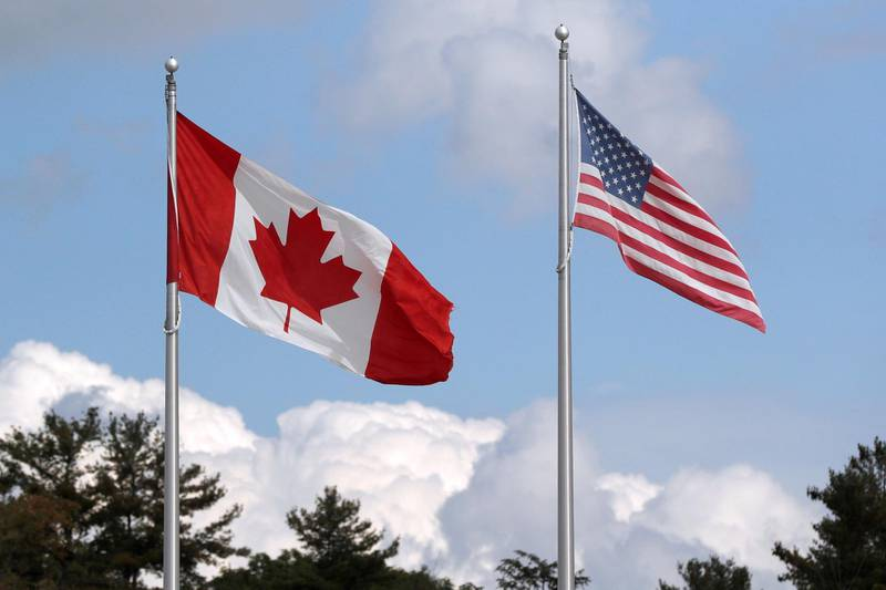 FILE PHOTO: A U.S. and a Canadian flag flutter at the Canada-United States border crossing at the Thousand Islands Bridge, which remains closed to non-essential traffic to combat the spread of the coronavirus disease (COVID-19) in Lansdowne, Ontario, Canada September 28, 2020.  REUTERS/Lars Hagberg/File Photo