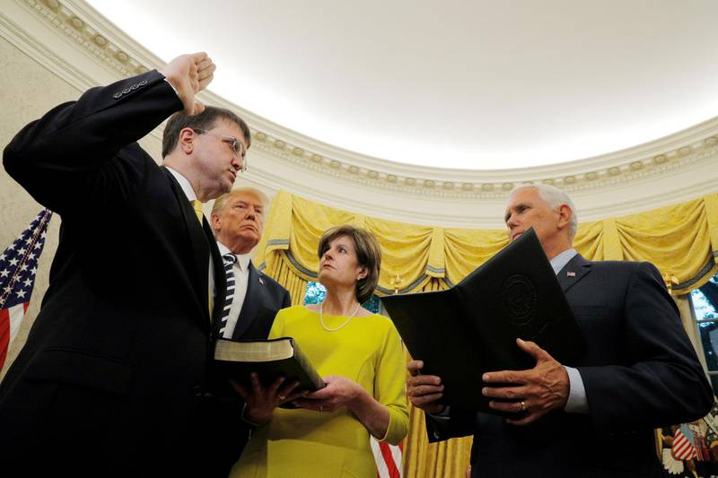 U.S. Vice President Mike Pence swears in Robert Wilkie as U.S. Veterans Affairs Secretary as President Donald Trump and Wilkie's wife Julia look on in the Oval Office at the White House in Washington, July 30, 2018.   REUTERS/Brian Snyder