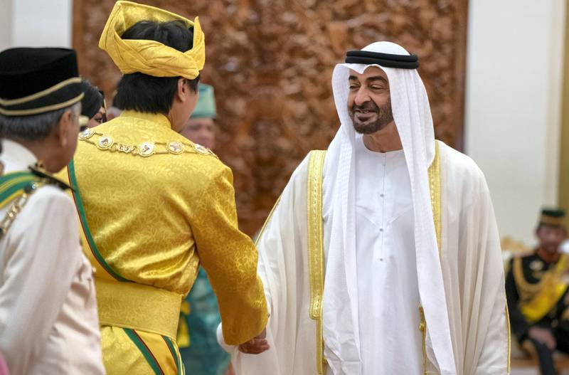 KUALA LUMPUR, MALAYSIA - July 30, 2019: HH Sheikh Mohamed bin Zayed Al Nahyan, Crown Prince of Abu Dhabi and Deputy Supreme Commander of the UAE Armed Forces (R) greets a guest during the inauguration of HM King Abdullah Ri'ayatuddin Al-Mustafa Billah Shah of Malaysia (not shown), at Istana Negara, the National Palace of Malaysia.( Rashed Al Mansoori / Ministry of Presidential Affairs )---