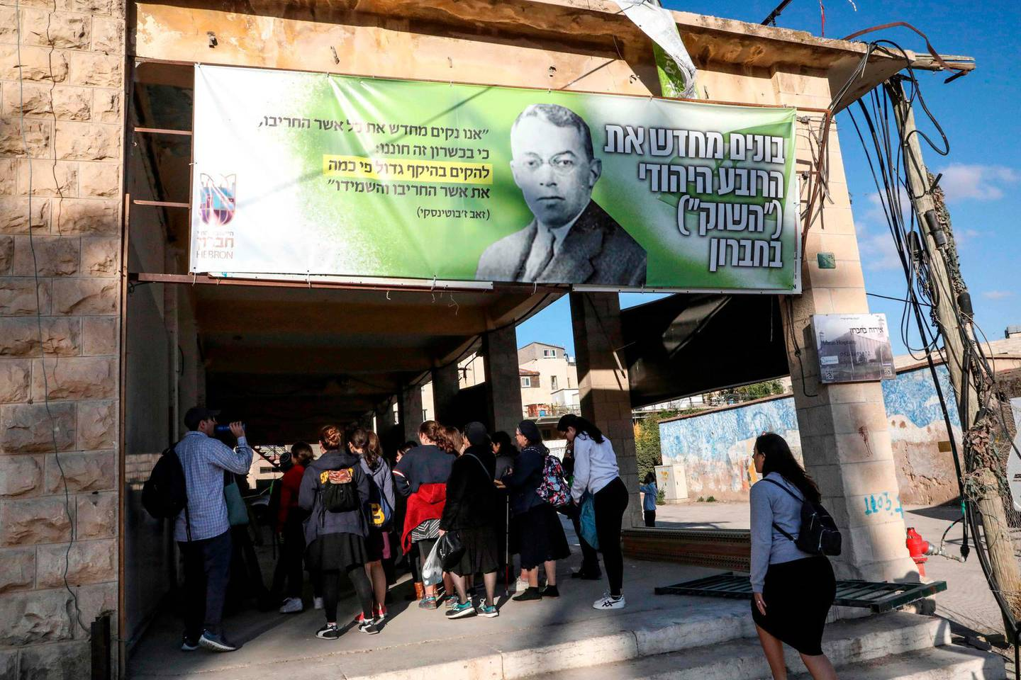 """Israeli visitors walk below a banner showing the portrait of late Zionist leader Ze'ev Jabotinsky and text in Hebrew (R) reading """"Rebuilding the Jewish Quarter 'The Market' in Hebron"""", as they enter an old market building along al-Shuhada street in the flashpoint city of Hebron in the occupied West Bank on December 1, 2019, following an announcement by the new Israeli hard-right defence minister to start planning a new Jewish neighbourhood in the wholesale market complex. Defence Minister Naftali Bennett's announcement came as the prospects of a third snap election since April loomed larger, with his New Right party leaning heavily on settlers for support at the polls. The market area is on Hebron's once-bustling Shuhada Street, now largely closed off to Palestinians, and which leads to the holy site where biblical patriarch Abraham is believed to have been buried. / AFP / HAZEM BADER"""
