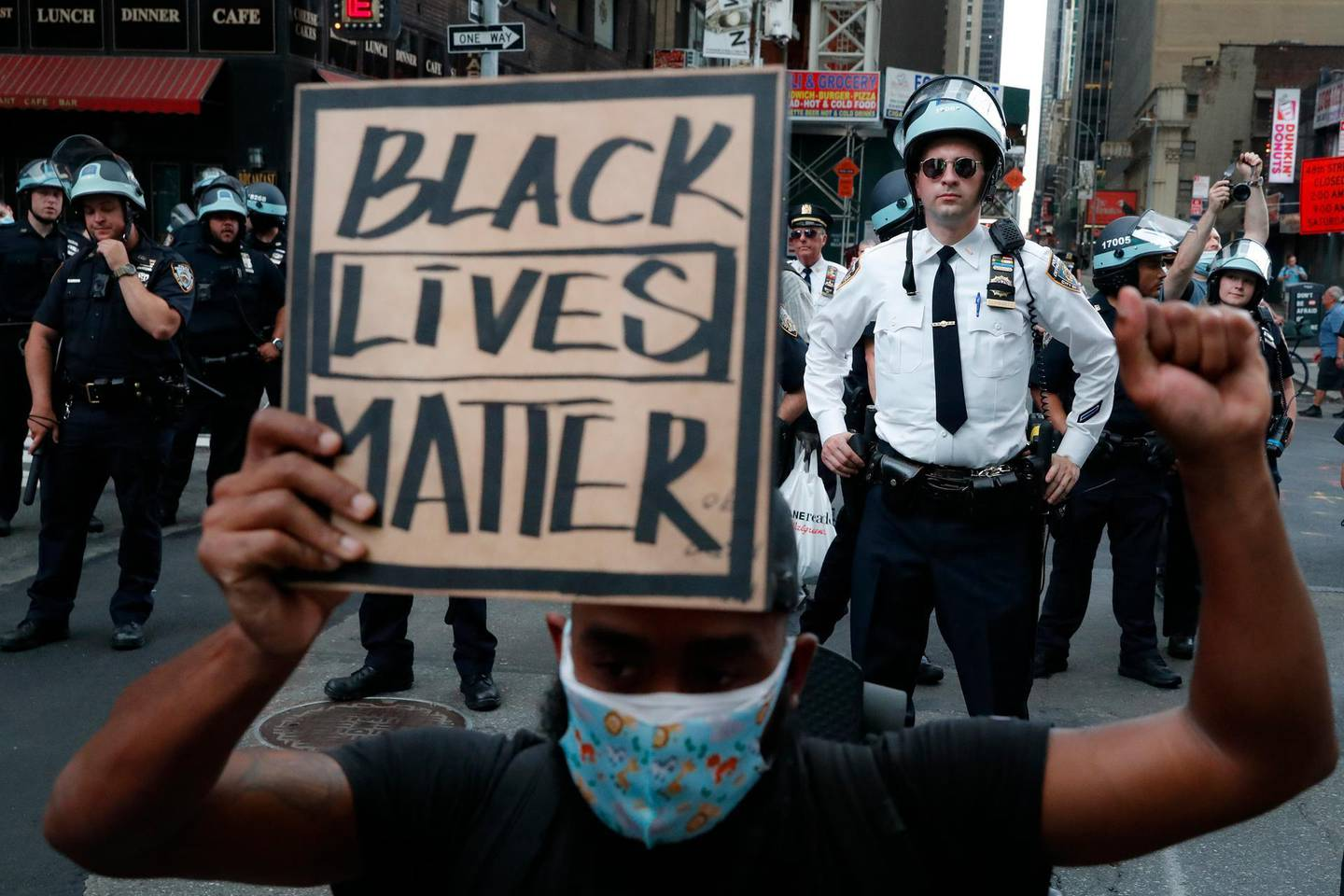 Police officer tail a group of protesters marching past Times Square, Thursday, June 4, 2020, in the Manhattan borough of New York. Protests continued following the death of George Floyd, who died after being restrained by Minneapolis police officers on May 25. (AP Photo/John Minchillo)