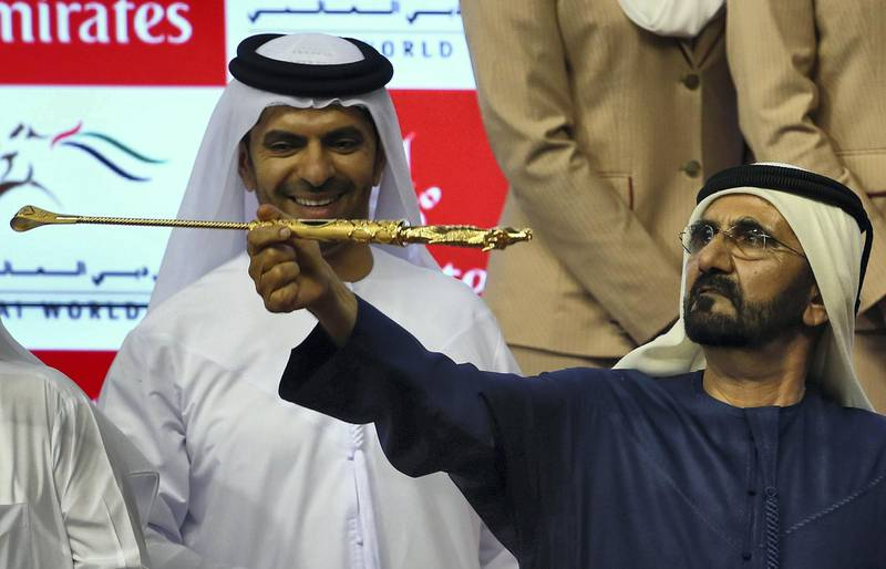Sheikh Mohammad Bin Rashid al-Maktoum, ruler of Dubai, spins the golden whip as he celebrates after his horse African Story won the Dubai World Cup, the world's richest horse race, at the Meydan race track in the Gulf Emirate on March 29, 2014. A cosmopolitan gathering of horses from seven different countries contested the US$10 million Emirates Dubai World Cup. AFP PHOTO/MARWAN NAAMANI (Photo by MARWAN NAAMANI / AFP)