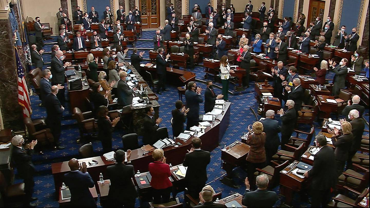 In this image from video, senators and staff give a standing ovation to U.S. Capitol Police offer Eugene Goodman, shortly before voting to award him the Congressional Gold Medal for his actions during the Jan. 6 riot, as the Senate took a break from the second impeachment trial of former President Donald Trump in the Senate at the U.S. Capitol in Washington, Friday, Feb. 12, 2021. (Senate Television via AP)