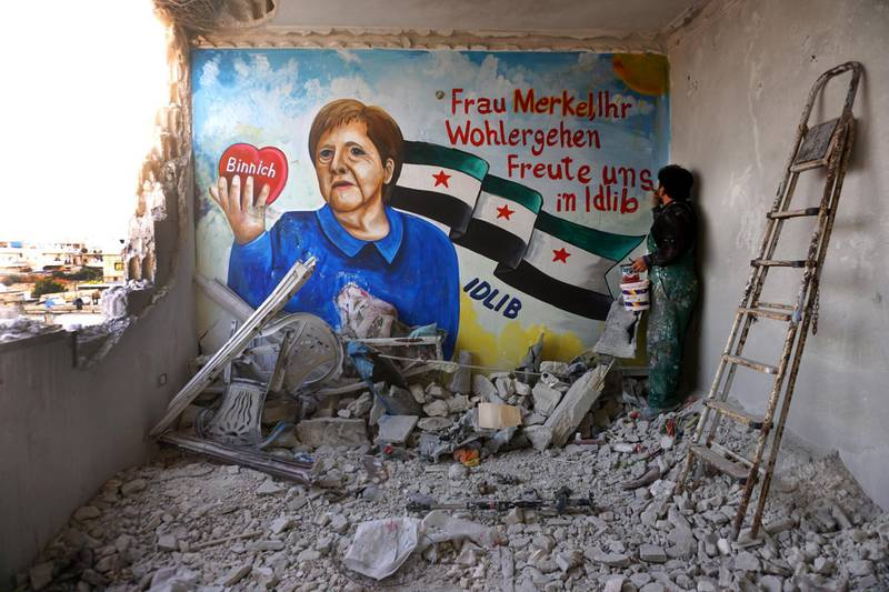 Artist Aziz al-Asmar paints a mural wishing for the well-being of German Chancellor Angela Merkel, who is in quarantine after being treated by a doctor who tested positive for coronavirus (COVID-19), inside a damaged building in the town of Binnish in Syria's northwestern Idlib province on March 24, 2020. (Photo by Muhammad HAJ KADOUR / AFP)